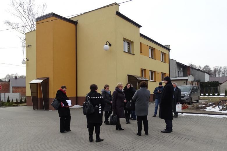 Ludzie stoją porzed piętrowym żółtym budynkiem