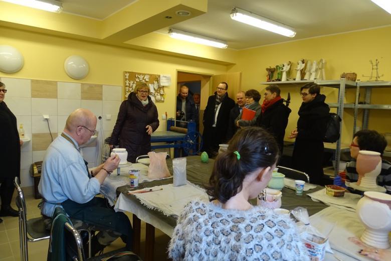 Ludzie siedzą przy stole i malują ceramikę