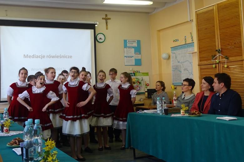 Dzieci w amarantowo-białych strojach śpiewają, goście siedzą przy zielonym stole