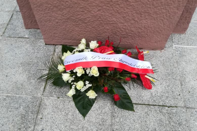 Wieniec białych i czerwonych kwiatów ze wstęgą z napisem Rzecznik Praw Obywatelskich