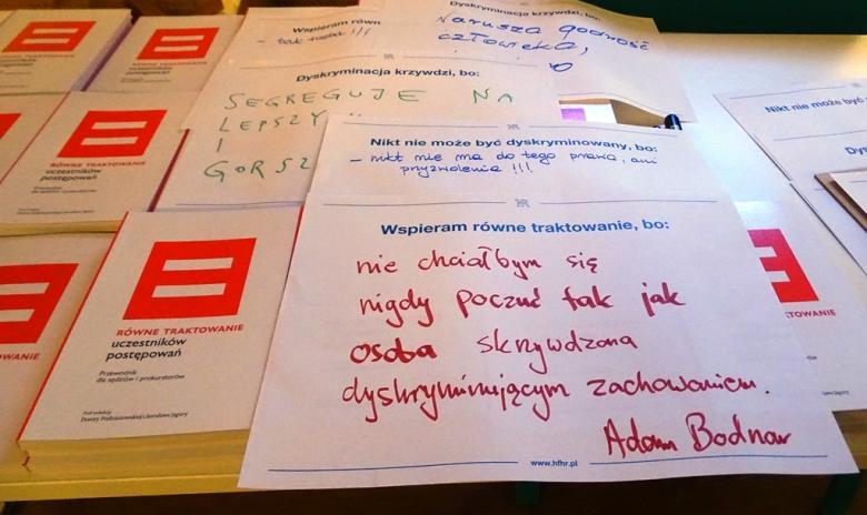 """Zdjęcie stołu: kartka z drukowanym napisem """"Wspieram równe traktowanie, bo ..."""" uzupełniona odręcznie czerwonym flamastrem: """"nie chciałbym się nigdy poczuć jak osoba skrzywdzona dyskryminującym zachowaniem. Adam Bodnar"""""""