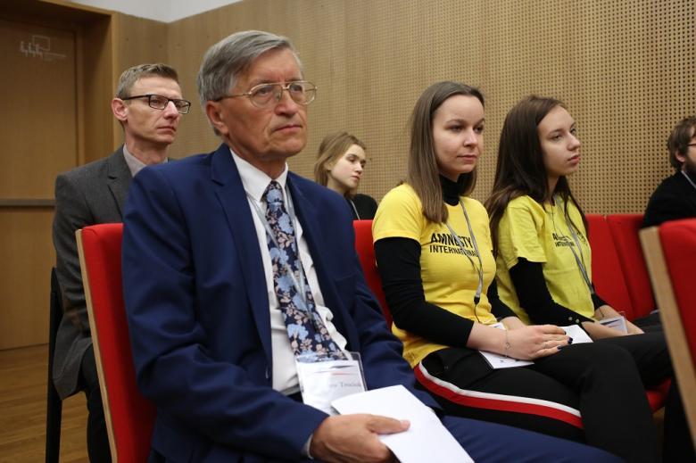 Uczestnicy panelu czerwone krzesła. Mężczyzna w garniturze i dwie kobiety w żólych koszulkach AI