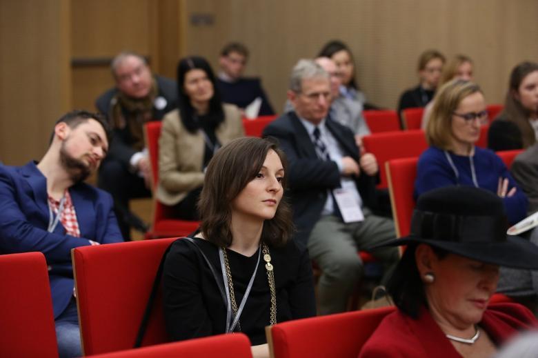 Uczestnicy panelu, czerwone krzesła, na pierwszym planie młoda kobieta