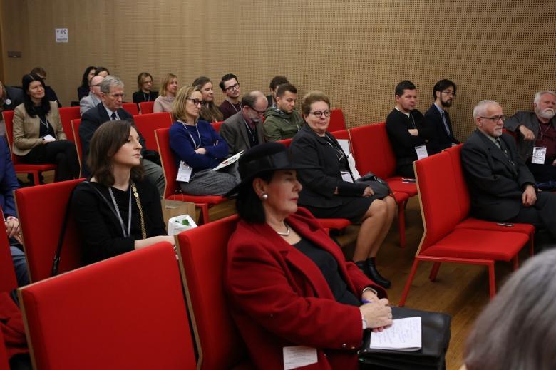 Uczestnicy panelu słuchają dyskusji, czerwone krzesła