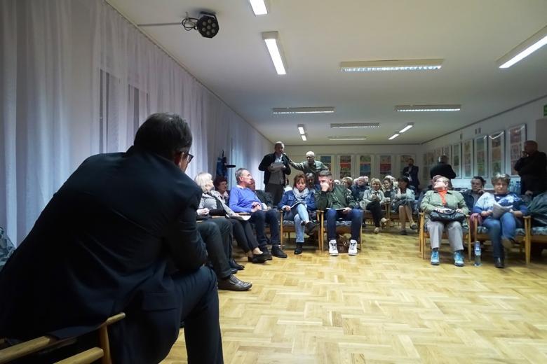 Mężczyzna pokazuje plik dokumentów, ludzie siedzą w kręgu
