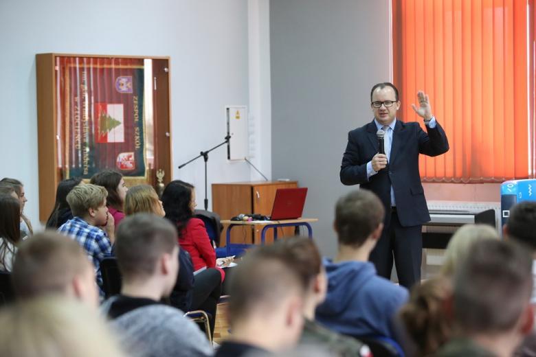 Mężczyzna mówi gestykulując do młodych ludzi