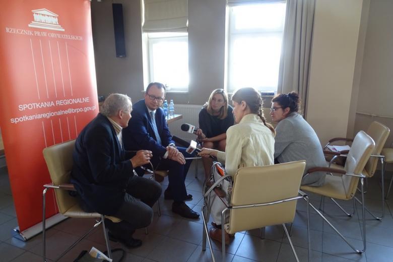 Zdjęcie: dziennikarze siedzą i słuchają odpowiedzi dwóch soób