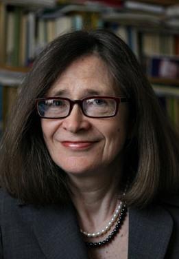 Kobieta w okularach na tle półek z książkami