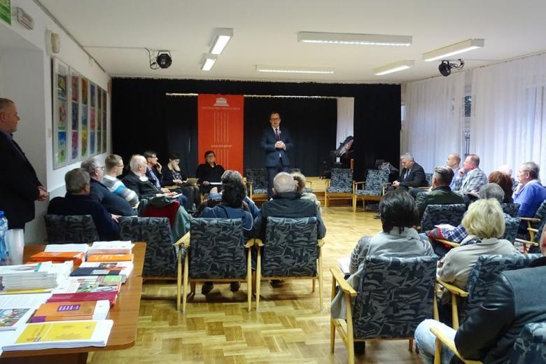 zdjęcie: kilka osób siedzi na fotelach przed nimi stoi mężczyzna w garniturze