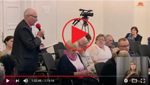 zdjęcie: na sali siedzi kilkadzisiąt osób, jeden z mężczyzn stoi i mówi do mikrofonu