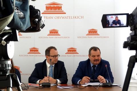 zdjęcie: dwóch mężczyzn siedzi za stołem na pierwszym planie widać obiektywy skierowanych w nich kamer