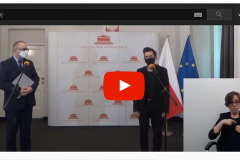 Dwaj mężczyźni przy mikrofonach, sylwetka tłumaczki PJM w rogu