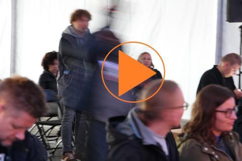 """Ludzie w namiocie, pomarańczowy znak """"play"""""""