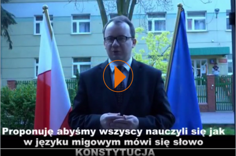 Zdjęcie: Adam Bodnar na tle flag Polski i UE oraz zielonych drzew. W tyle budynek