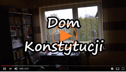 """Zdjęcie ze znakiem """"play"""": mieszkanie i napis """"Dom Konstytucji"""""""
