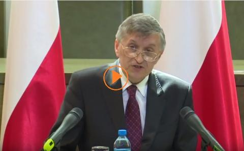 zdjęcie: mężczyzna w garniturze przemawia, za nim widać polskie flagi