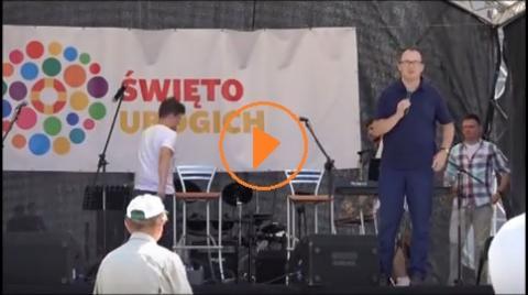Mężczyzna na scenie mówi do mikrofonu, znak PLAY