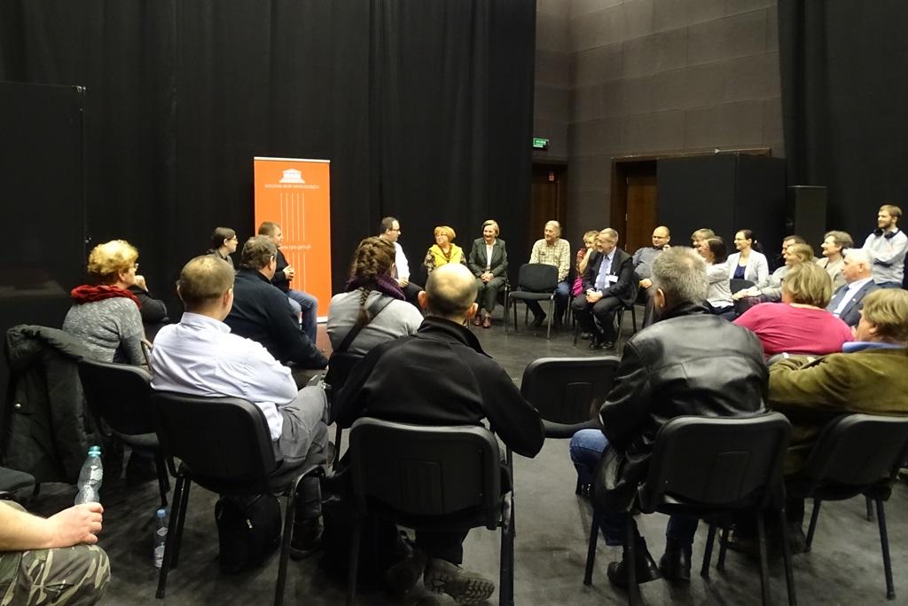 W pomieszczeniu o ciemnych ścianach duża grupa ludzi rozmawia siedząc w kręgu