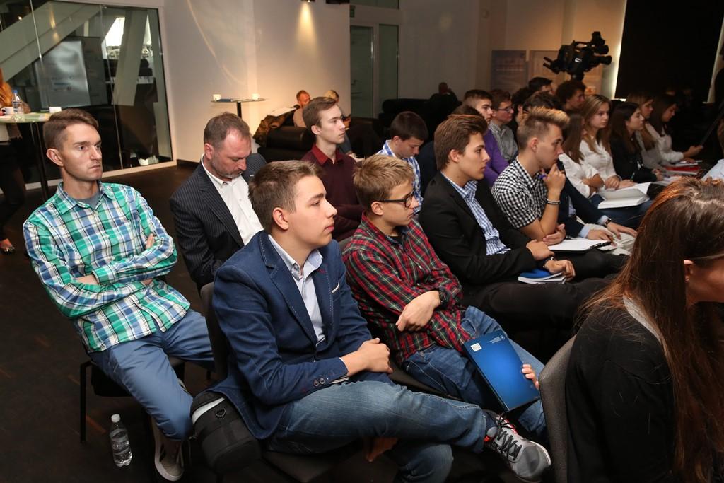 Młodzi ludzie przysłuchują się debacie