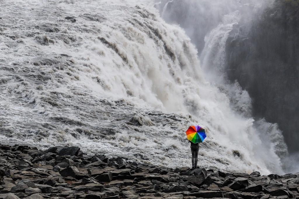 Osoba z tęczową parasolką wobec wzbierającej fali wodospadu