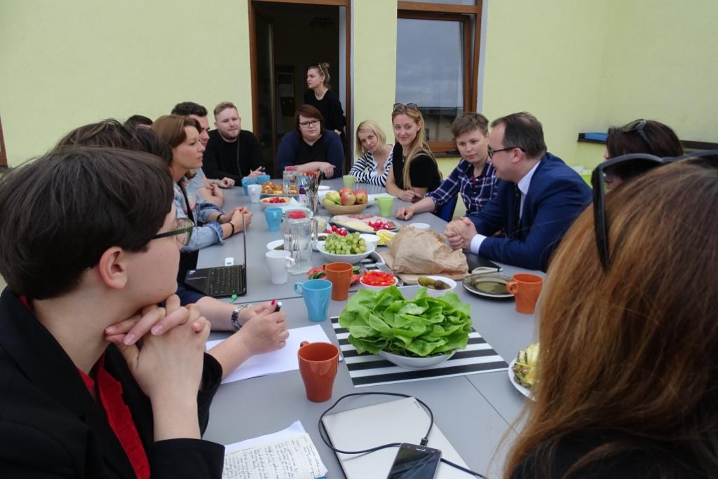 Ludzie przy stole na dużym tarasie, na stole sałata i sery