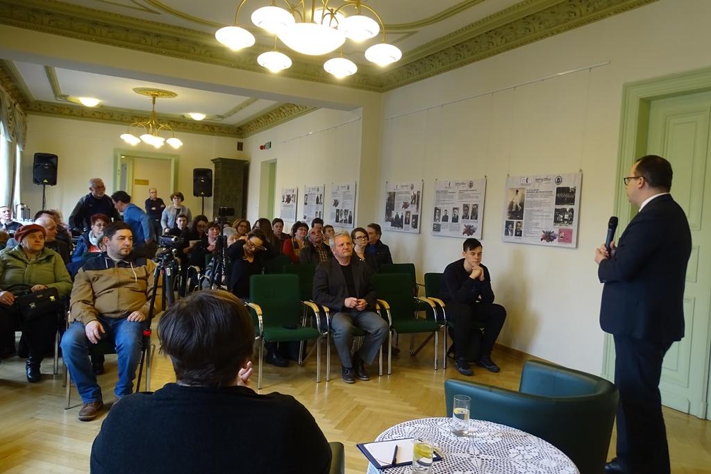 Ludzie siedzą na sali, widok od przodu na twarze uczestników