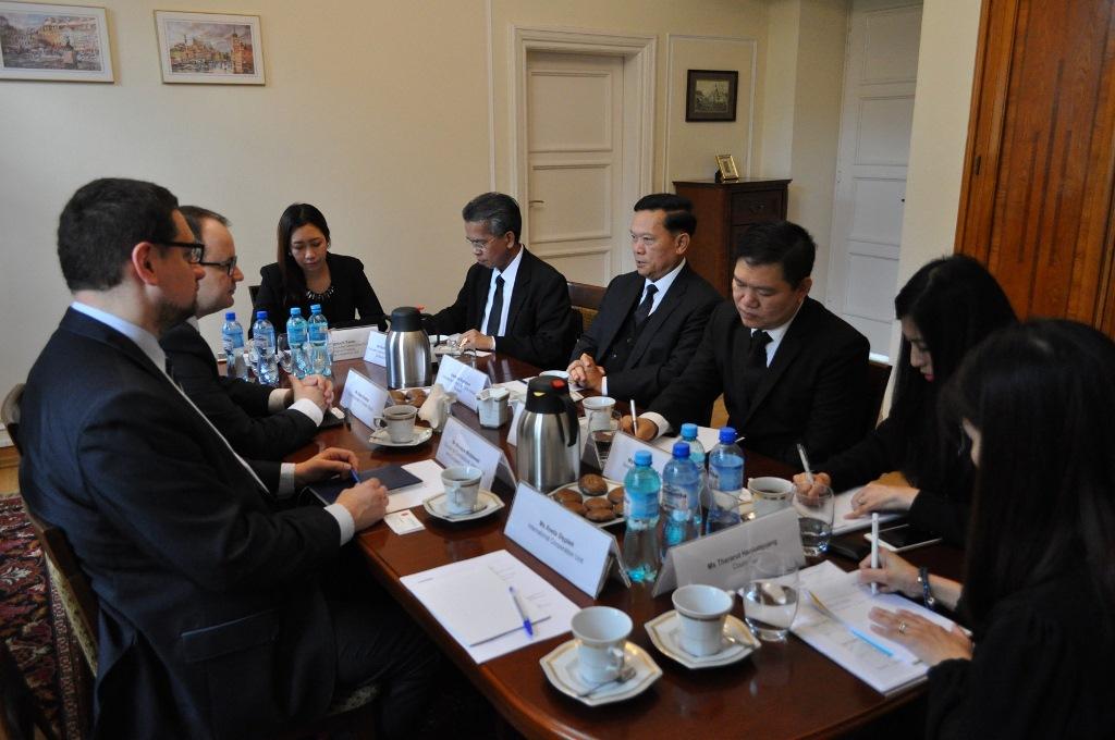 zdjęcie: kilka osób siedzi przy podłużnym brązowym stole