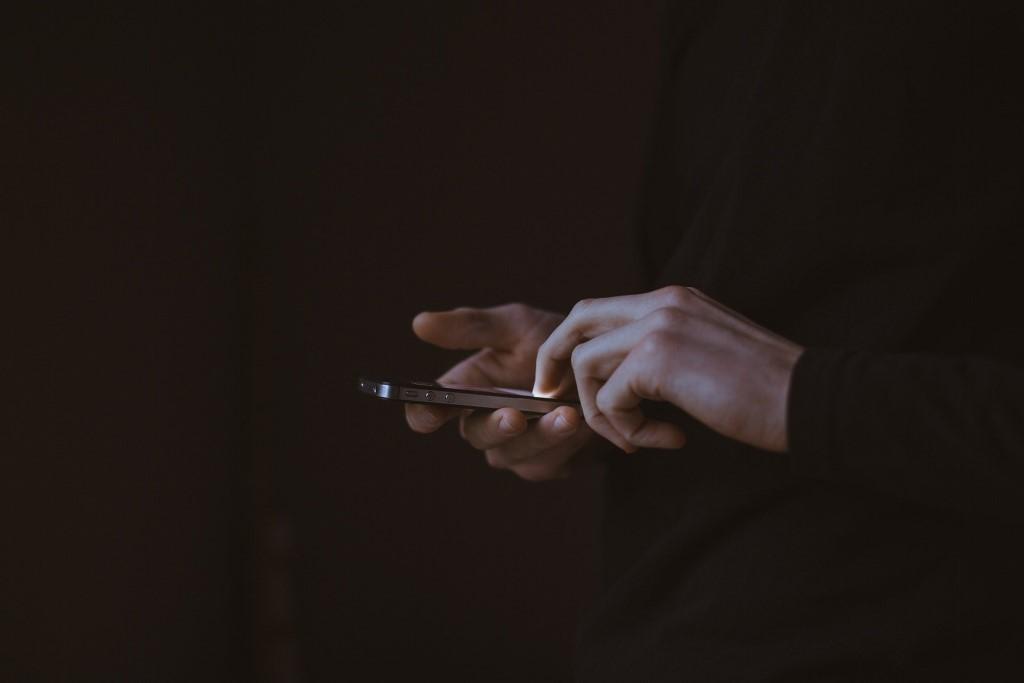 Człowiek używa telefonu w ciemności