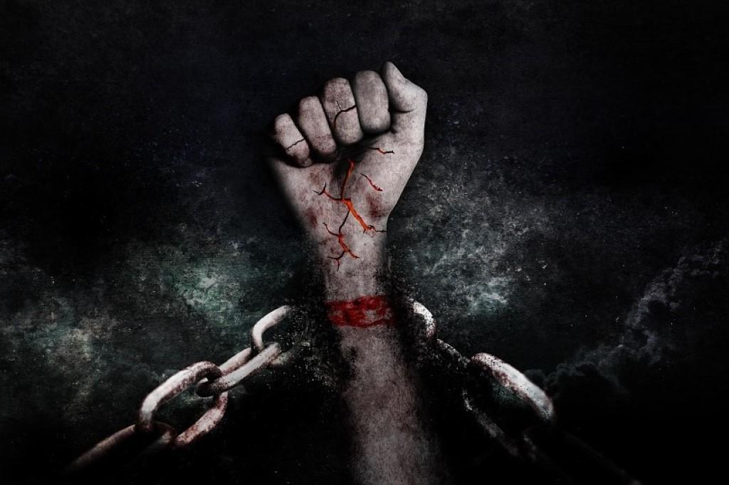 zdjęcie ręki wyrywającej się z kajdan