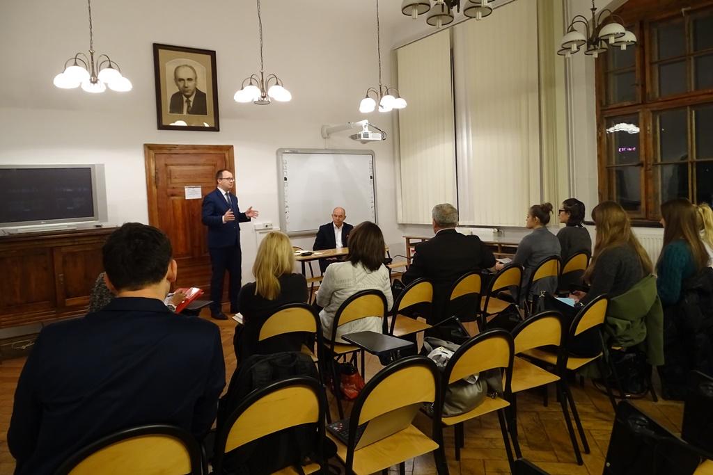 Zdjęcie: Kilkanaście osób na sali wykładowej, mężczyzna mówi na stojąco