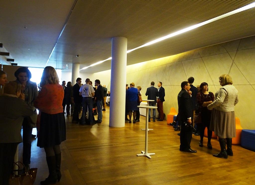 Zdjęcie: ludzie rozmawiają w grupach na korytarzu