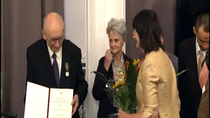 Mężczyzna odbiera dyplom od kobiety, obok kobieta z odznaczeniem