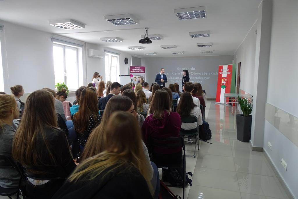Jasna sala lekcyjna, uczniowie siedzą na krzesłach ustawionych w rzędach, męzczyzna mówi