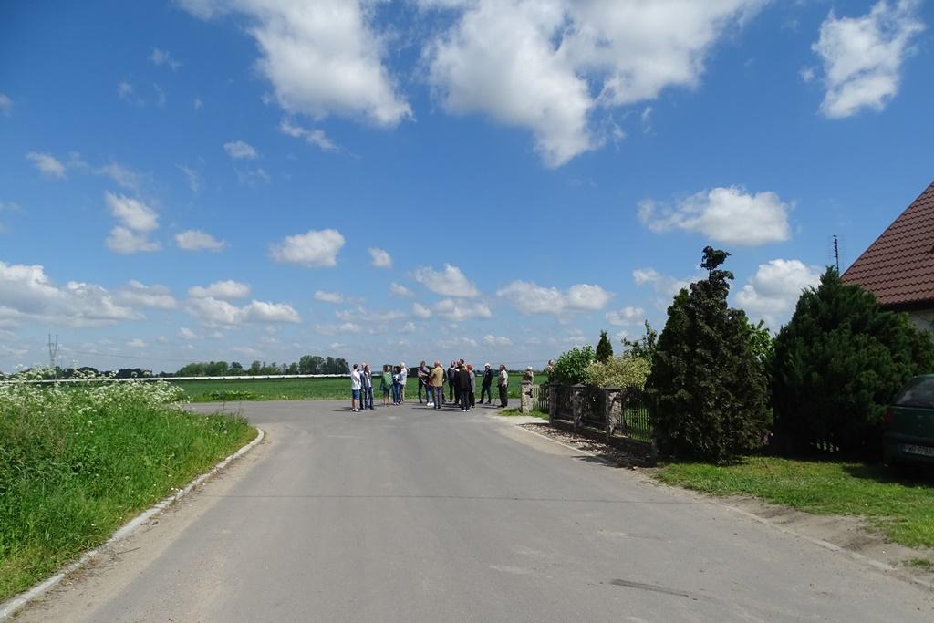 Droga wzdłuż pola, na horyzoncie - fermy