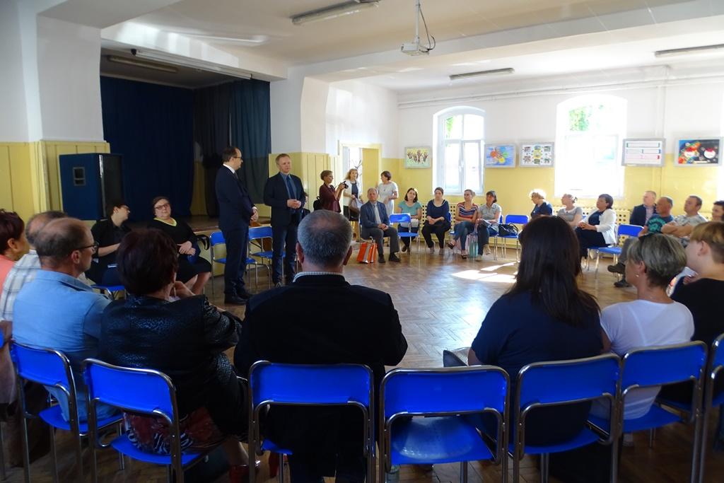 Ludzie siedzą w kręgu na niebieskich krzesłach