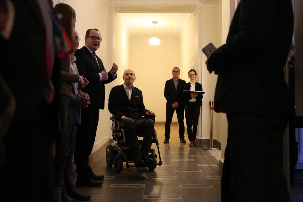 Kilka osób, w tym mężczyzna na wózku, na korytarzu