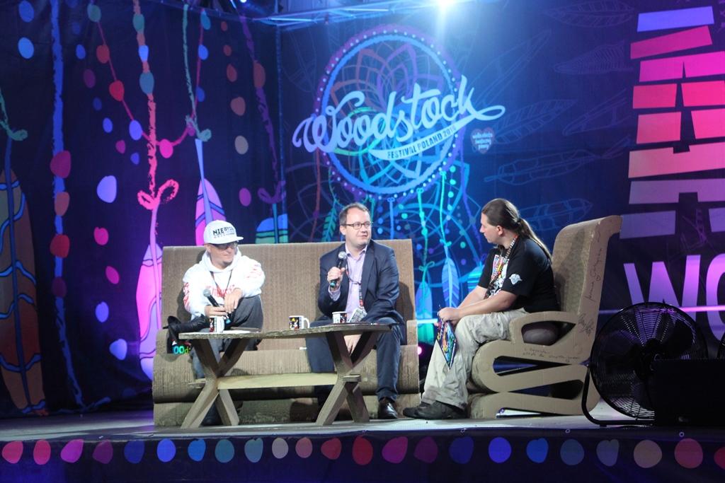 zdjęcie: na scenie siedzą trzej mężczyźni i rozmawiają