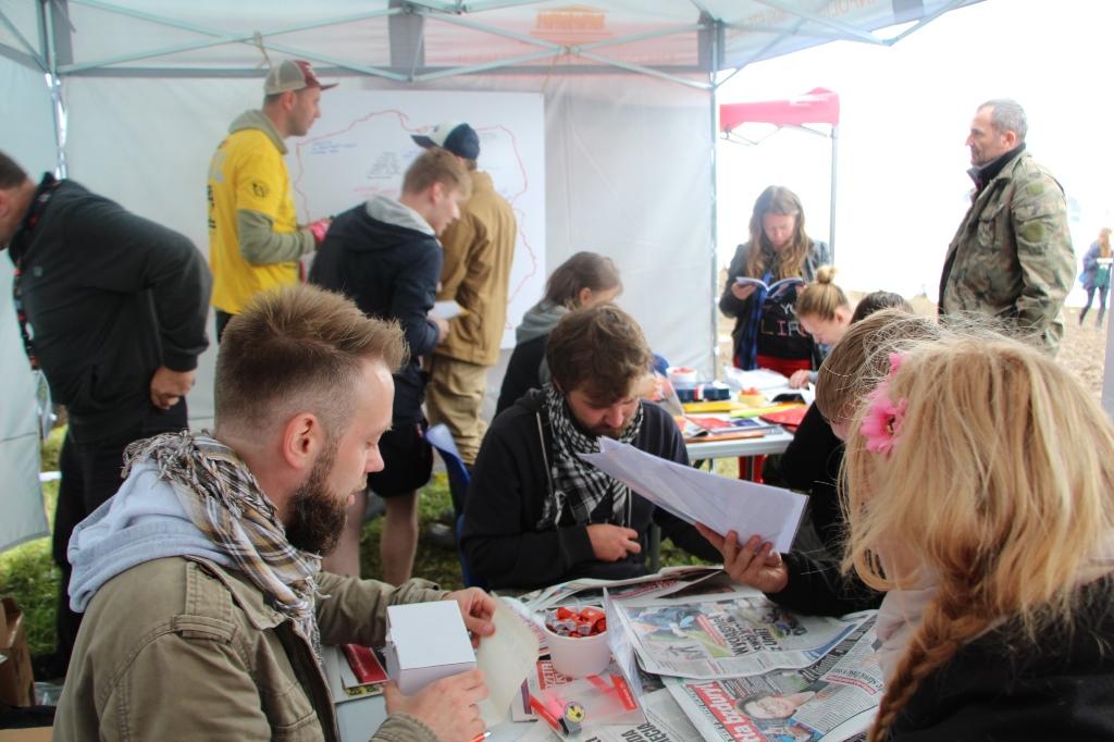 zdjęcie: ludzie siedzą w namiocie przy dwóch stolikach, na stołach kolorowe gazety