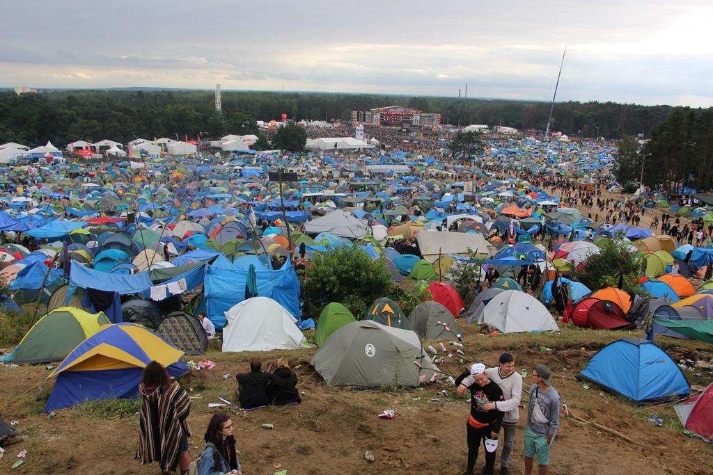 zdjęcie: wielkie pole namiotowe, w tle duża scena muzyczna
