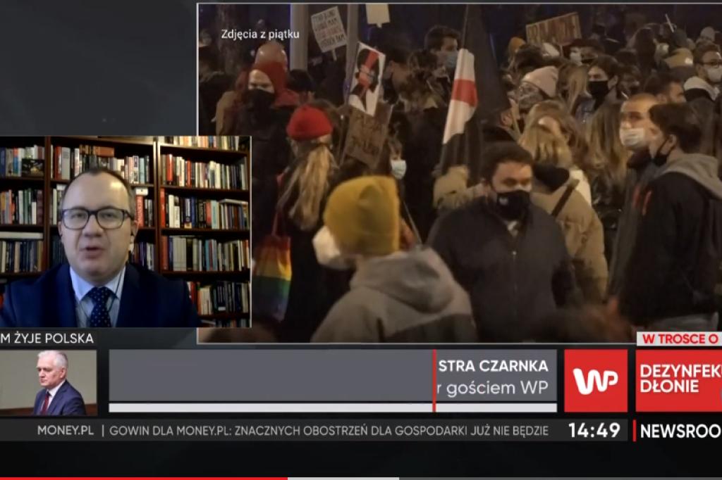 Screen ekranu: protestujący ludzie i mężczyzna na tle książek