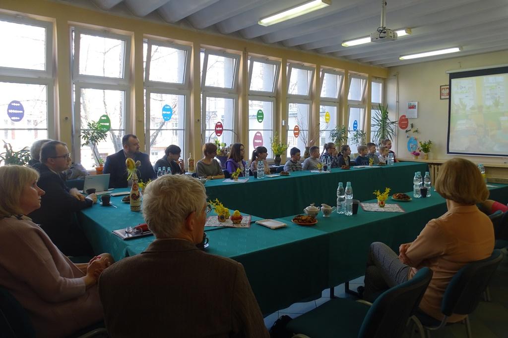 Dzieci i dorośli siedzą przy stole pokrytym zielonym suknem