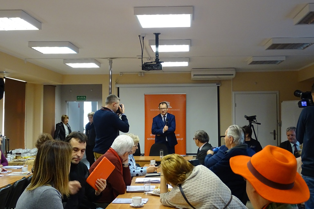Zdjęcie: ludzie siedzą przy równoległych stołach, mężczyzna stoi na baneru RPO, na pierwszym planie kobieta w pomarańczowym kapeluszu