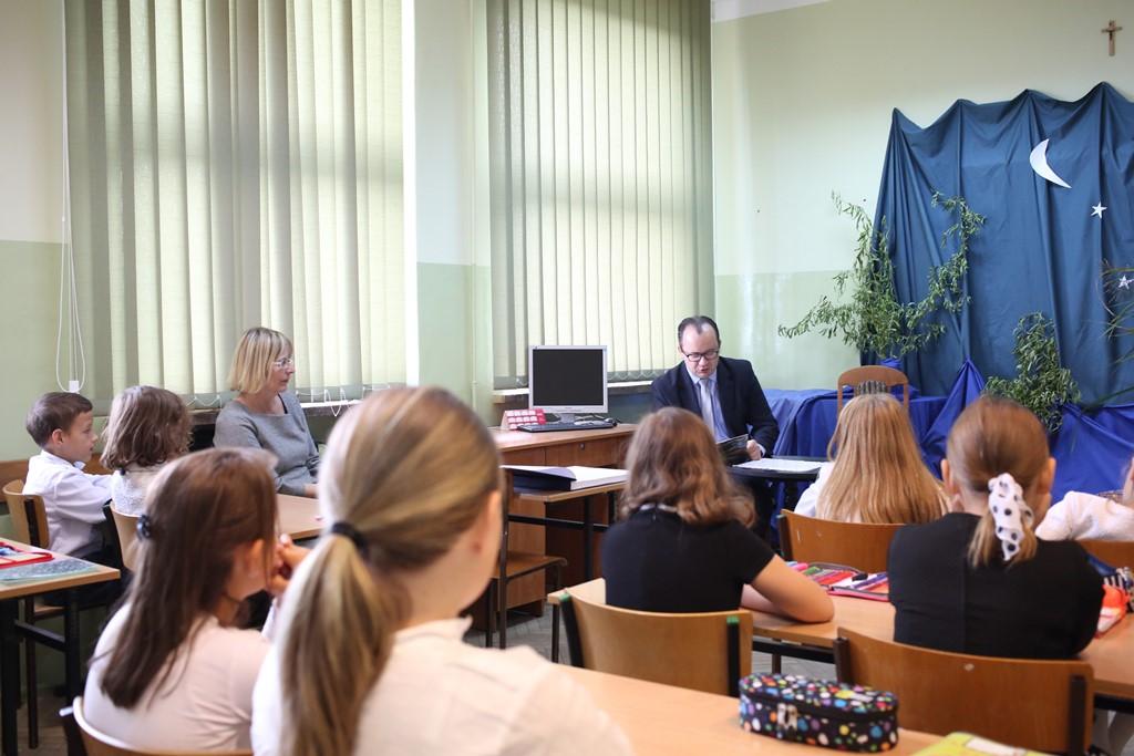 Mężczyzna w klasie czyta uczniom książkę
